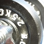 A close up shot of a dark grey dumbbell.