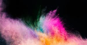 Holi powder blowing up on black background.