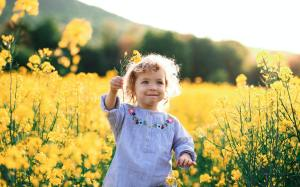 Front view of happy small toddler girl running in nature in rapeseed field
