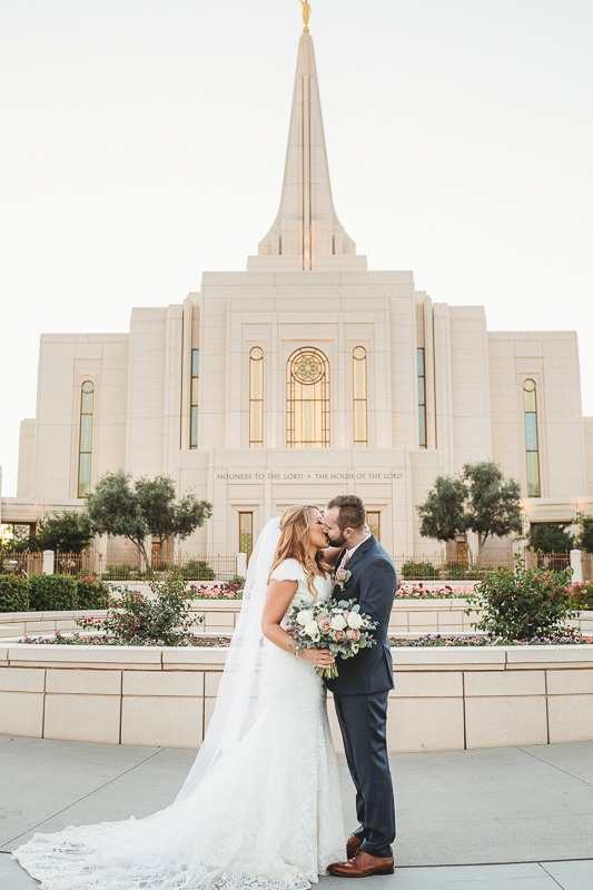 wedding photos of bride and groom kissing in front of the gilbert arizona temple