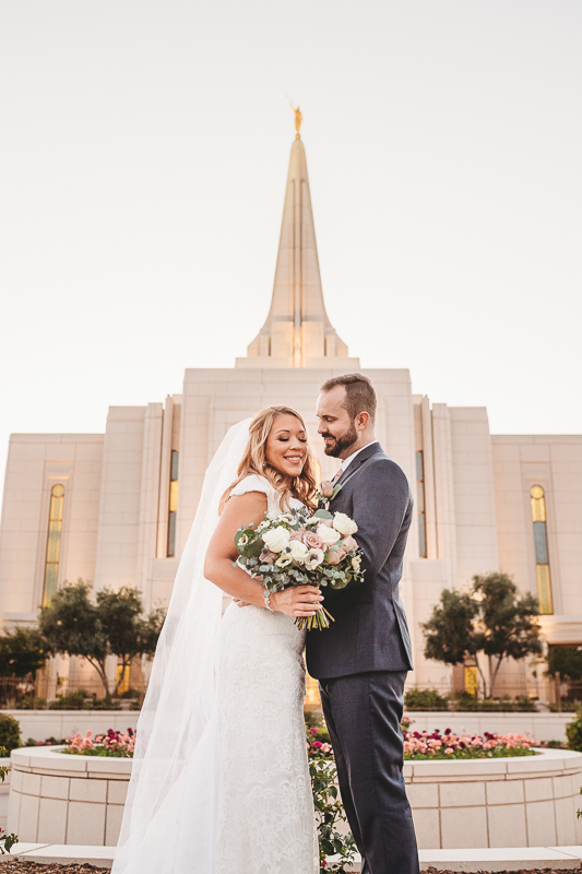 LDS temple wedding bride and groom holding bouquet in front of Gilbert Temple