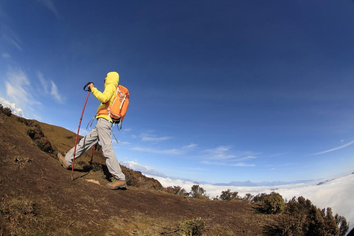 young woman backpacker climbing to mountain peak