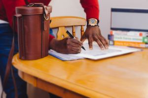 Person signing papers with leather bag on wooden table