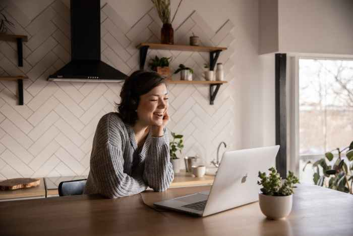 smiling woman talking via laptop in kitchen