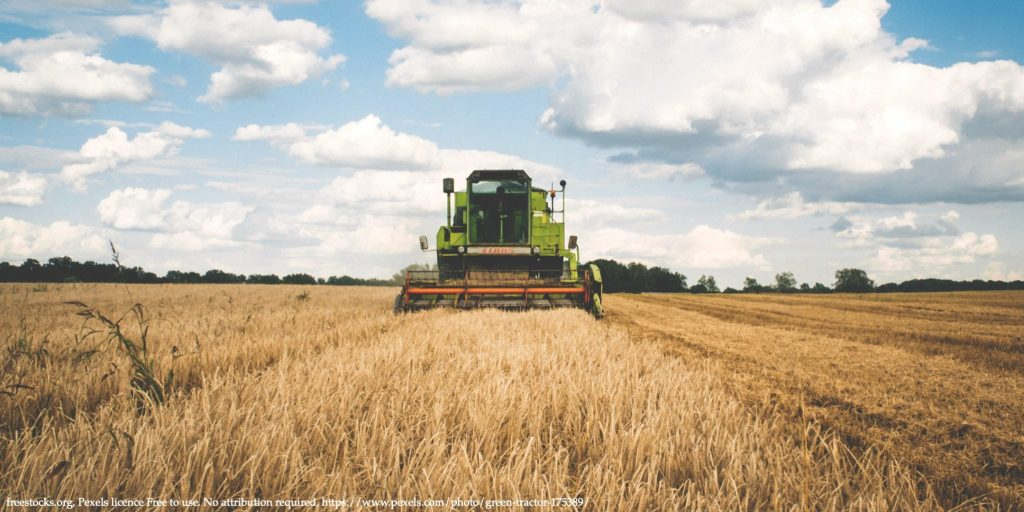 An image of the wheat field with with grain harvester representing food security