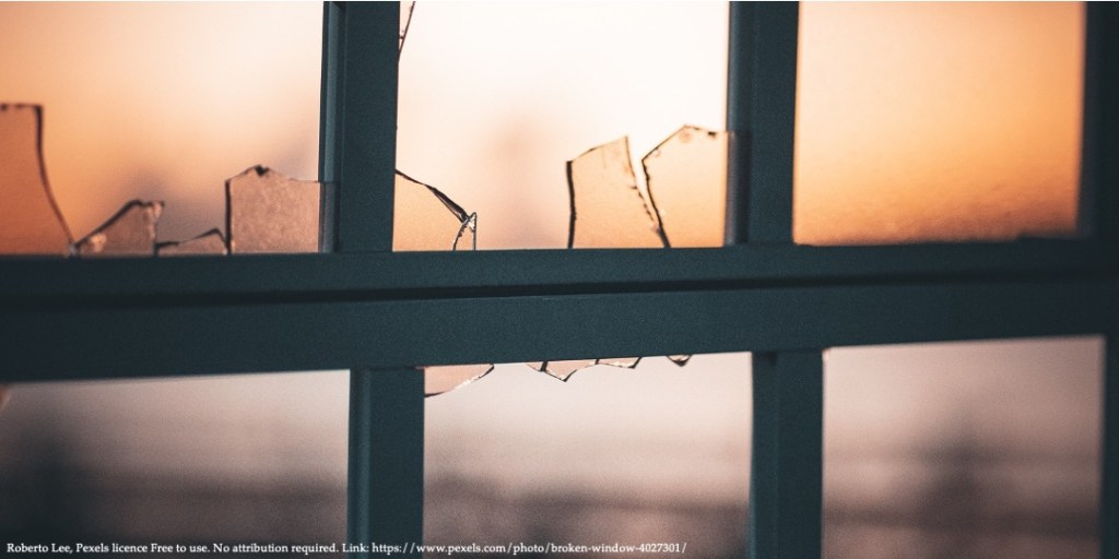 A view of a window with broken glass representing representing perspectives of domestic violence