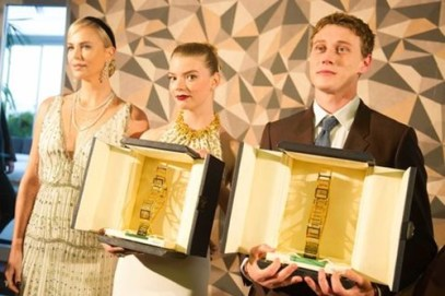 Anya Taylor-Joy (middle) receiving the Trophee Chopard with George MacKay and Charlize Theron