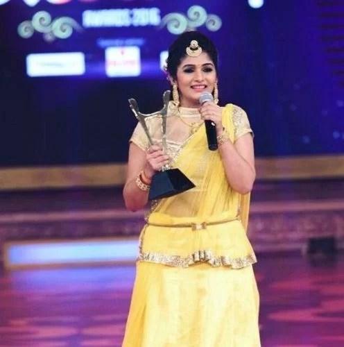 Divya Suresh holding her award