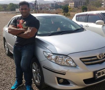 Jagdish Lad posing with his car