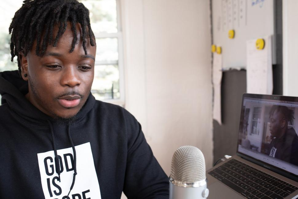 Young Male Vlogger with mic and laptop