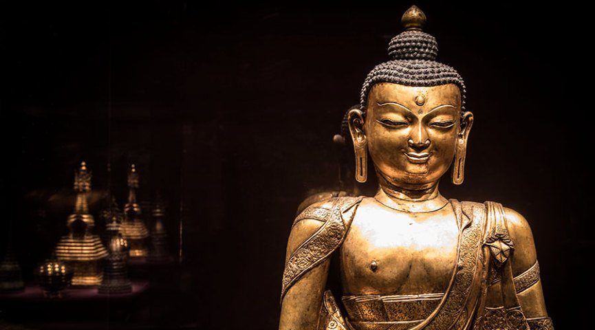 A golden buddha with less visible objects in the background, from a gallery shot of Encountering the buddha