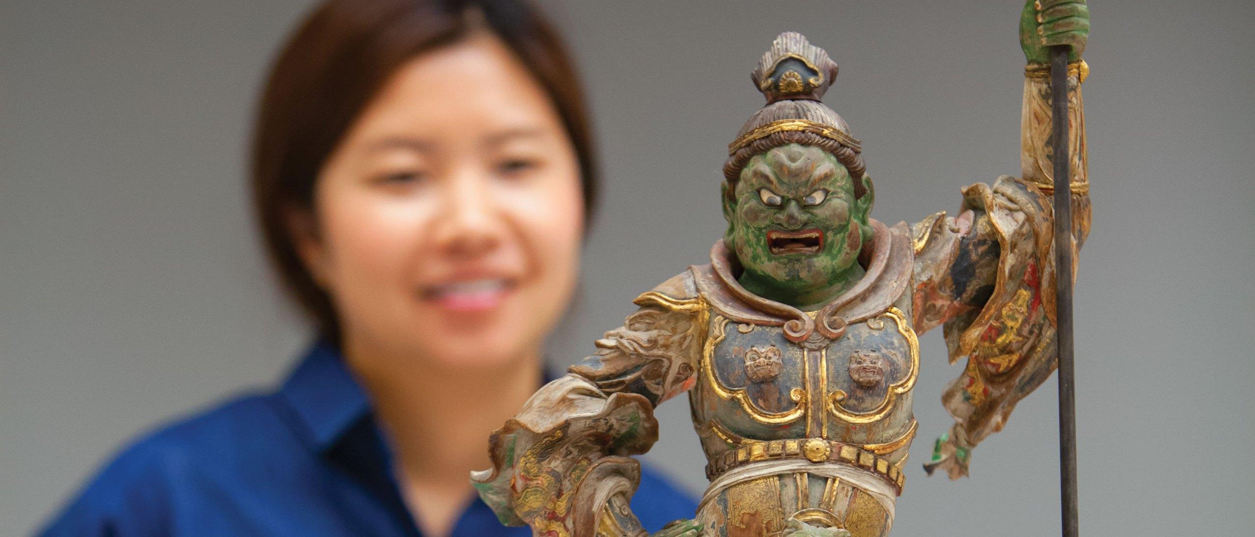 A woman admires a Japanese sculpture