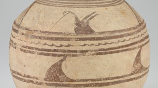 light brown round jar with dark brown painted design of bird and lines