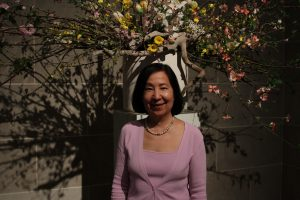 Ann Yonemura, in pink top, standing in gallery.