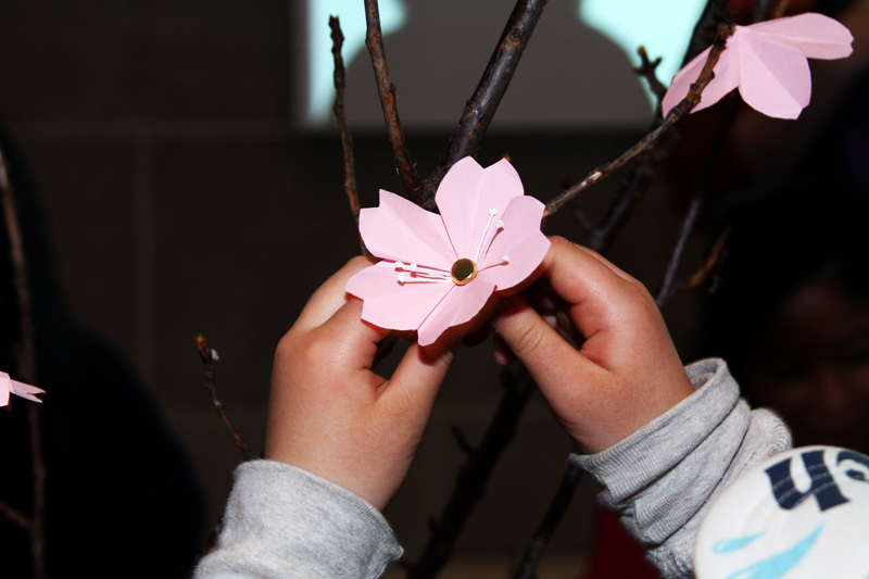Branch with pink origami cherry blossoms - small hands grasp the bottom of closest blossom.
