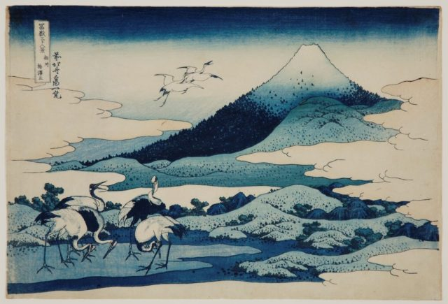 Mount Fuji with birds standing in front and in the air on left - all in shades of blue.