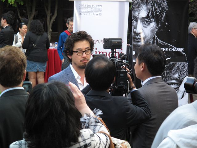 Director Na Hong-jin surrounded by press.