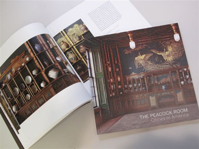 The Peacock Room book open to image of shelves in room (left) and closed book (right).