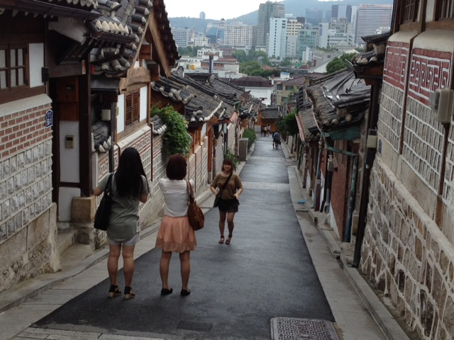 Narrow downhill street with houses on each side. Two women at top of street facing downhill, one woman below them facing uphill.