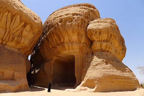 Large sandstone natural element in desert, with carved entrance.