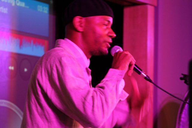 Close up of DJ Spooky holding microphone - in pink light.