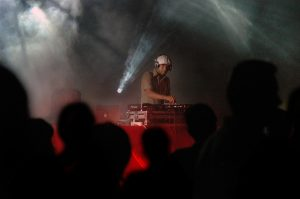 DJ Spooky on stage, mixing at table.