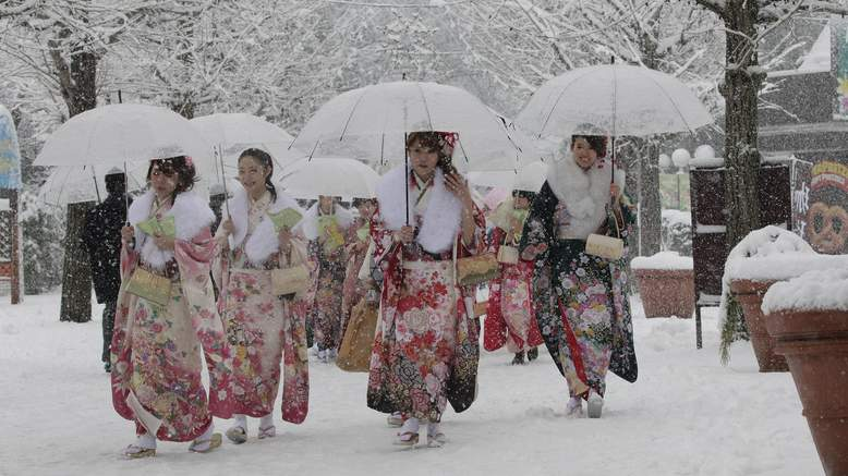 Several young women dressed in elaborate kimonos and fur stoles walk in the snow holding umbrellas