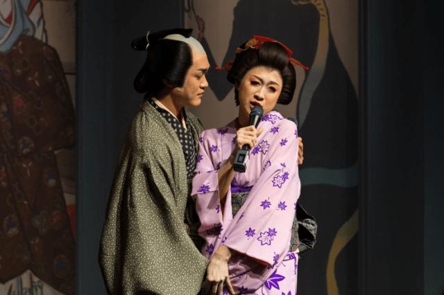 Actor portraying Utamaro holds the actress portraying Okita Naniwaya