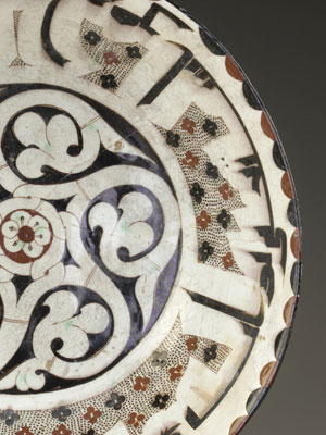 Ceramic bowl decorated with floral patterns and calligraphy in enamel.