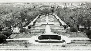 detail from a black and white photo, non-running fountain and trees along side