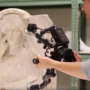 a man holding a large camera to 3D scan a white carved sculpture of a female face