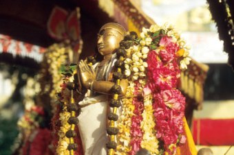 Bronze statue of Saint Appar, adorned with floral garlands