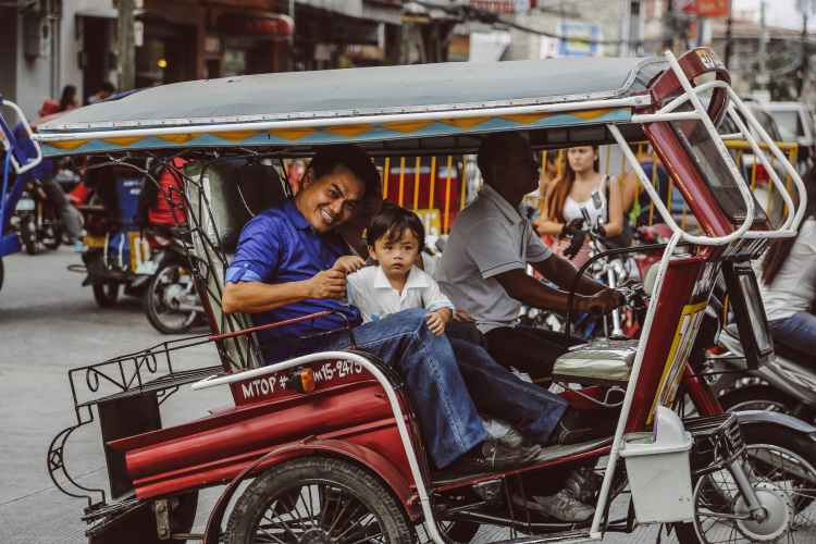 man and boy riding a tricycle