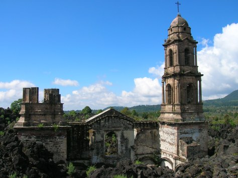 A ruined cathedral, partially buried by lava rock, against a background of blue sky, clouds, and tree-covered hills.