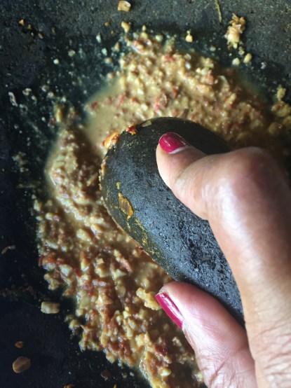 Pounding peanuts for satay sauce