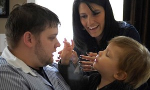 BotMultichillT_Adams_holds_his_three-year-old_son_while_(BCBA)_therapist_assists wikimedia commons