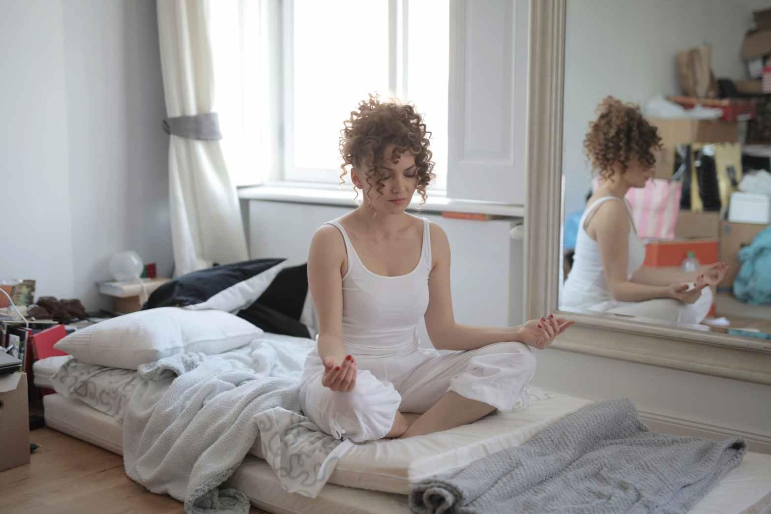 calm woman in lotus pose meditating after awakening at home
