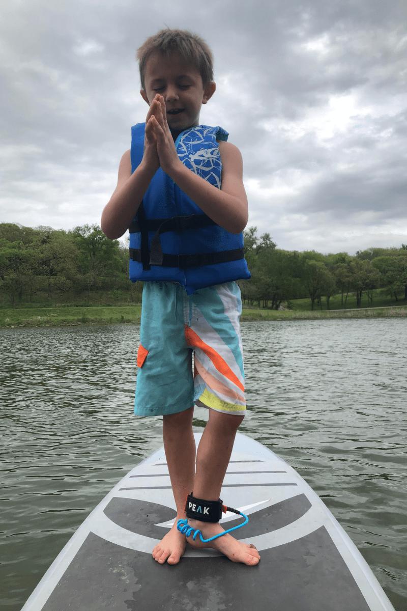 Meditating boy on Paddleoard