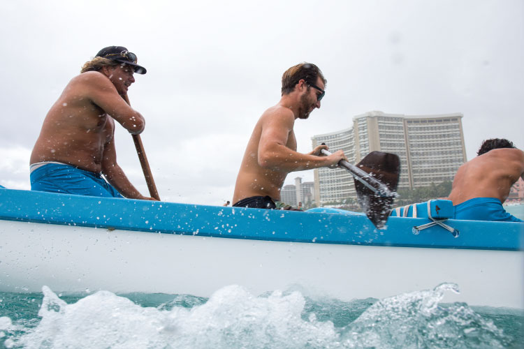 """""""This is just another day at the office,"""" said Zane Aikau (left) steering an outrigger canoe with writer Cash Lambert (middle). Photo: Heff"""