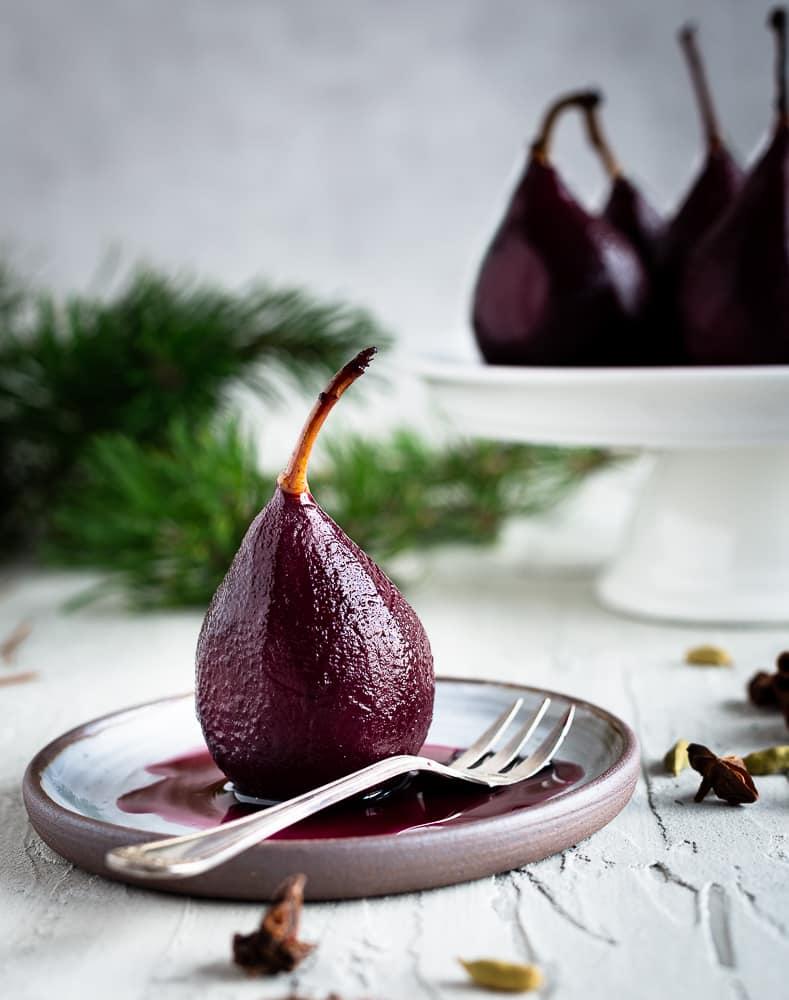 Des poires pochées dans un vin chaud épicé qui rappelle l'ambiance des marchés de Noël. Très photogéniques mais surtout délicieuses, ces poires sirupeuses feront sensation lors de vos dîners en famille ou entre amis pendant les fêtes !