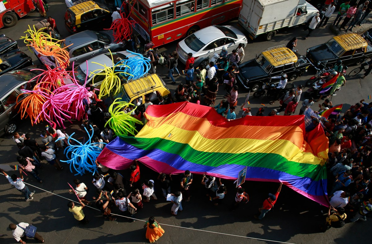 Participants holding a rainbow flag pass through a junction during a gay pride parade, which is promoting gay, lesbian, bisexual and transgender rights, in Mumbai, January 31, 2015. REUTERS/Danish Siddiqui (INDIA - Tags: SOCIETY) - RTR4NPD8