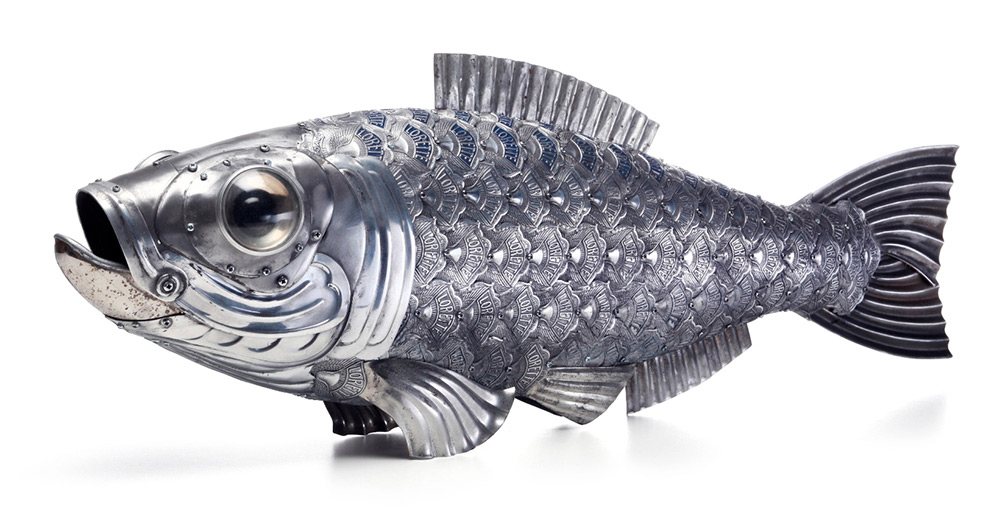 Sardine, 25 x 70 x 11 cm. BODY: Moped chain guard covered with multiple bicycle logo badges; HEAD: Solex front fenders, car bumpers. EYES: Flashlights; GILLS: Car door parts, bicycle chain guards. TAIL: Motorbike exhaust pipe; FINS: Cake tins.