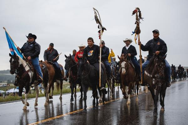 On Friday, August 20, rain poured on campsite participants as they headed toward a prayer ceremony near the construction site. Camp leader Jon Eagle mentioned that the horse nation brought the rain as good medicine. (Photo: Thosh Collins)