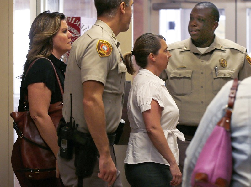 Tulsa Police officer Betty Shelby, right, being escorted into court for an early proceeding in her upcoming manslaughter trial in the killing of Terence Crutcher. CREDIT: AP Photo/Sue Ogrocki, File.