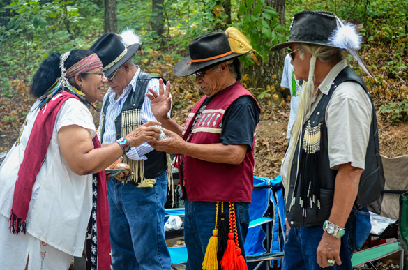 Three Georgia elders, from left, Charles Reyes-LittleEagle, GT Martinez, and Chumsey Harjo, being honored with gifts from officiant of the closing ceremony Bibi Vanessa Inaru Pastrano (Taino). (Amy Morris)