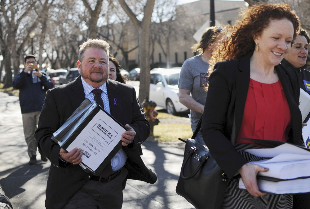 Trans man Terri Bruce helping deliver petitions against the anti-transgender bill back in February. CREDIT: AP Photo/James Nord.