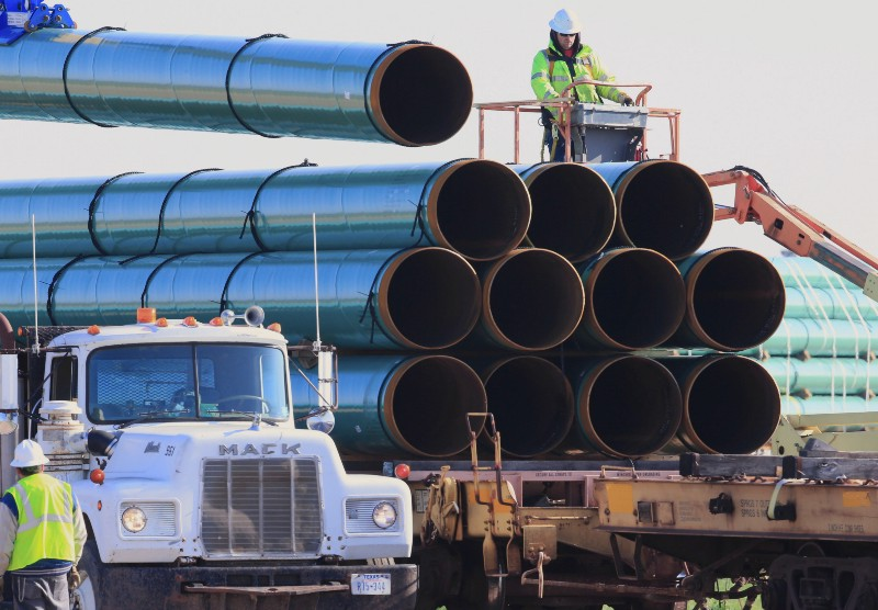 Workers unload pipes for the proposed Dakota Access oil pipeline. CREDIT: AP Photo/Nati Harnik, File.
