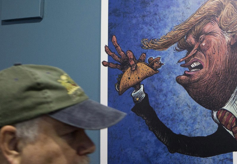 "An American visitor walks past a cartoon of a Mexican wrapped in a taco sticking his tongue out at a depiction of President-Donald Trump, in an exhibition titled; ""Trump: A wall of caricatures,"" at the Caricature Museum in downtown Mexico City CREDIT: AP Photo/Rebecca Blackwell."