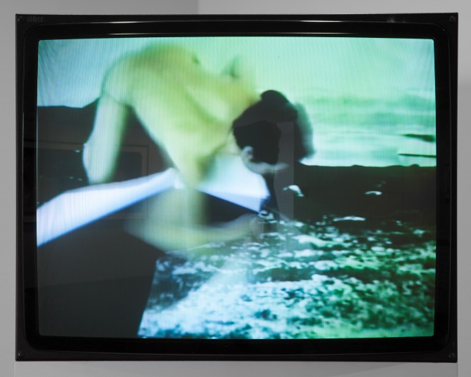 A still from Arke's 1996 video Arctic Hysteria shows the artist naked and crawling across a photograph of Nuugaarsuk Point in Greenland. Photo courtesy of the Louisiana Museum of Modern Art. Acquired with funding from Anker Fonden 