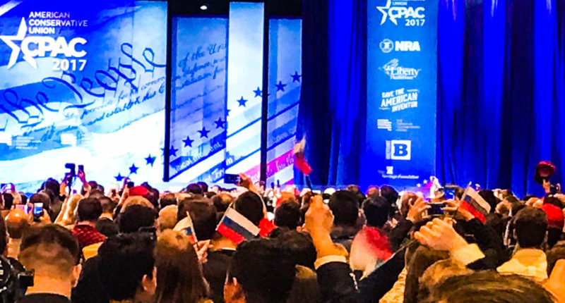 "CPAC attendees wave Russian flags with the word ""TRUMP"" written on the front (Screen cap)."